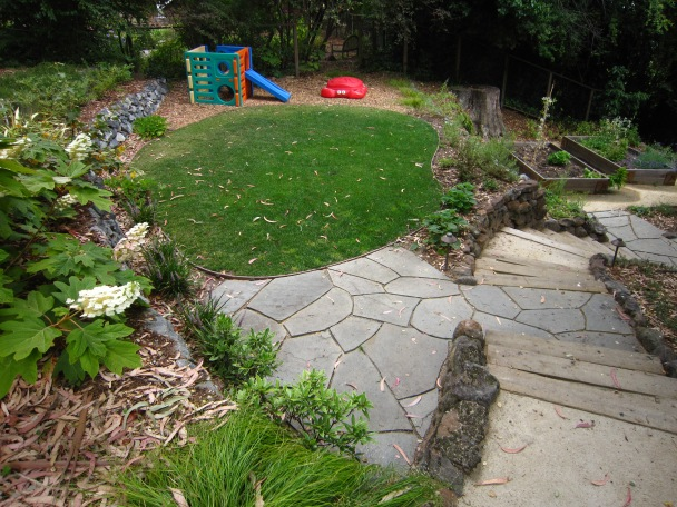 AFTER: Play room. Shade tolerant grass and playground fiber overlook the raised veggie boxes with blueberry patch above existing stone wall